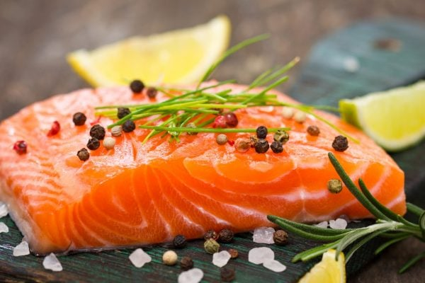 salmon fillet sprinkled rock salt peppercorns and herbs on a cutting board