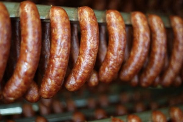 smoked sausages hanging in a row