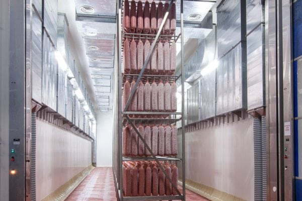 large salami curing room with several racks and many hanging salami